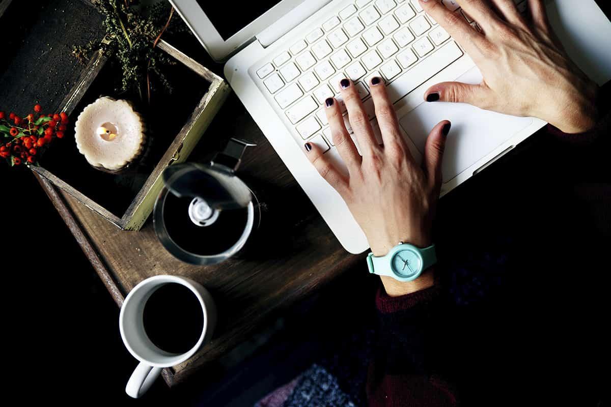 Ragazza che scrive a computer bevendo un caffè