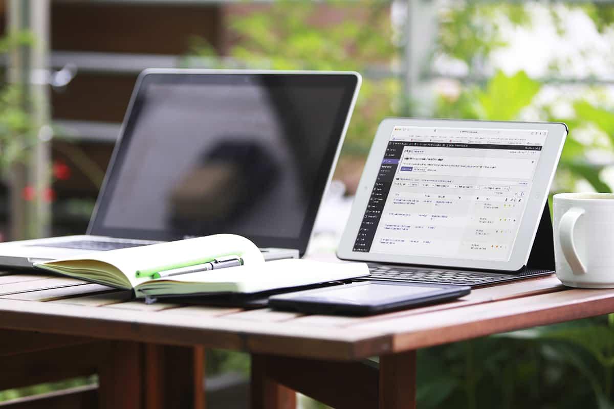Tavolo con due computer portatili e un quaderno aperto